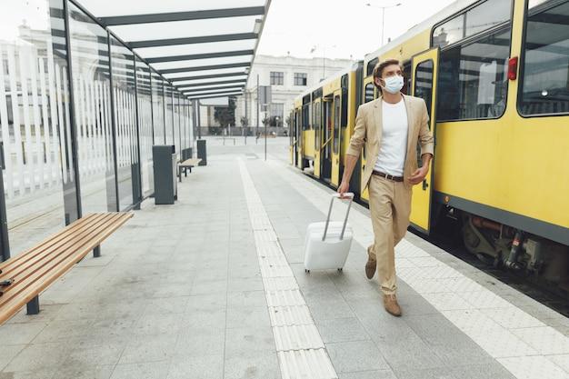 Ritratto integrale dell'uomo bello in vestito di affari e mascherina medica che cammina alla fermata del trasporto pubblico con i bagagli