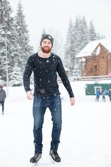 Ritratto a figura intera di un bell'uomo che pattina sul ghiaccio all'aperto con la neve