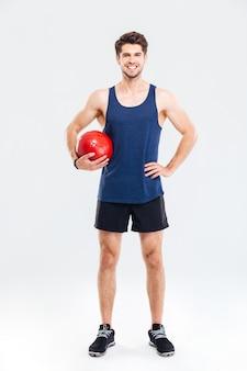 Ritratto a figura intera di un bell'uomo che si allena con una palla fitness isolata su uno sfondo grigio