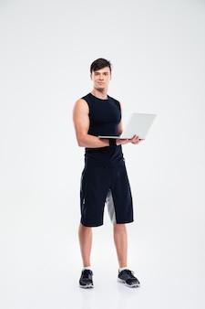 Ritratto a figura intera di un bell'uomo sportivo in piedi con un computer portatile isolato