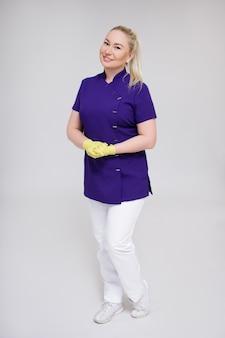 Ritratto a figura intera di felice infermiera, estetista o cosmetologo in uniforme in posa su sfondo grigio
