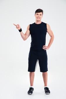 Ritratto integrale di un uomo felice di forma fisica che mostra il dito lontano isolato