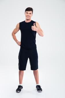 Ritratto integrale di un uomo felice di forma fisica che mostra pollice su isolato