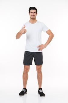 Ritratto a figura intera di un uomo felice di forma fisica che mostra i pollici in su isolato su uno sfondo bianco
