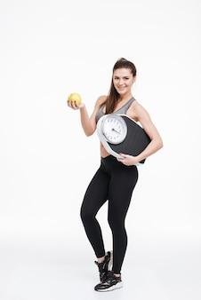 Ritratto a figura intera di una donna fitness sorridente felice in piedi, con in mano una mela e una bilancia isolata