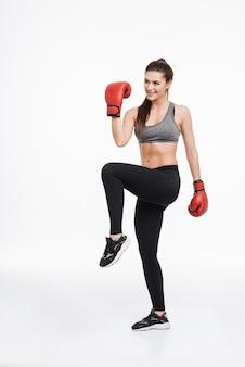 Ritratto a figura intera di una donna fitness sorridente felice che indossa guanti da boxe in piedi su un piede con il pugno in alto isolato