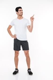 Ritratto a figura intera di un uomo sportivo sorridente felice in piedi e che punta il dito lontano isolato su uno sfondo bianco