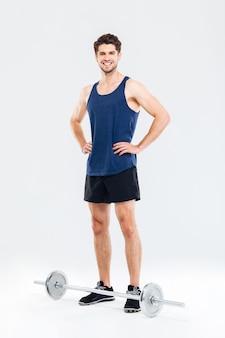 Ritratto a figura intera di uno sportivo sorridente felice pronto per iniziare un esercizio con un bilanciere isolato su uno sfondo grigio