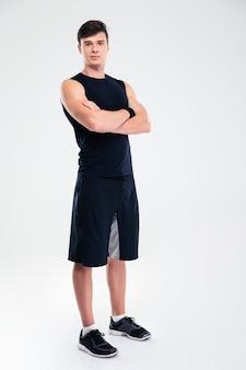Ritratto a figura intera di un uomo sportivo felice in piedi con le braccia conserte isolate