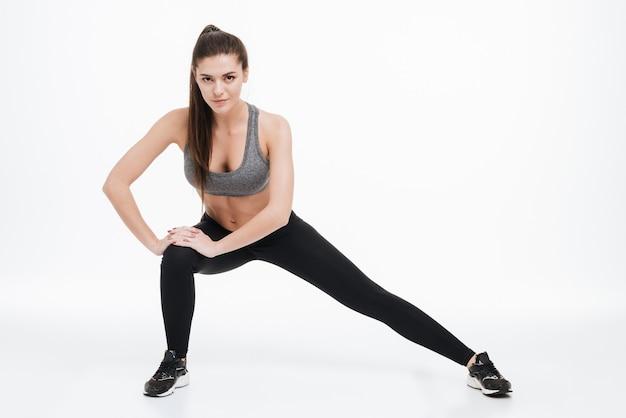 Ritratto a figura intera di una donna sportiva felice che allunga la gamba su una superficie bianca