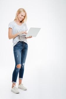 Ritratto a figura intera di una donna felice che utilizza un computer portatile isolato su un muro bianco