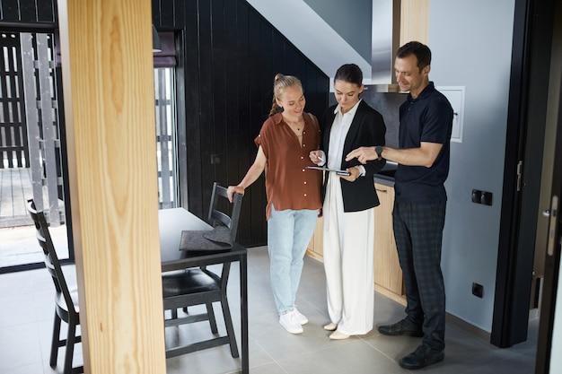 Ritratto a figura intera di una giovane coppia felice che parla con un agente immobiliare mentre acquista una nuova casa, copia spazio