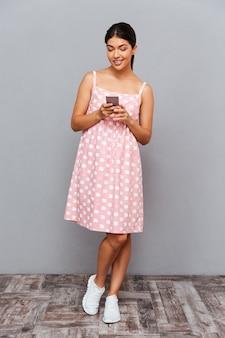 Ritratto a figura intera di una giovane ragazza felice che utilizza smartphone isolato su un muro grigio