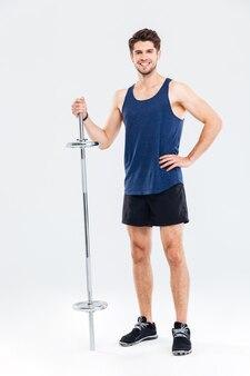 Ritratto a figura intera di un giovane sportivo felice in piedi con bilanciere isolato su uno sfondo grigio