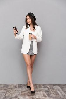 Ritratto integrale di una giovane donna felice vestita in minigonna e giacca su sfondo grigio, tenendo la tazza di caffè, utilizzando il telefono cellulare