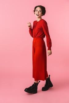 Ritratto integrale di una giovane donna felice che indossa vestiti rossi in piedi isolato