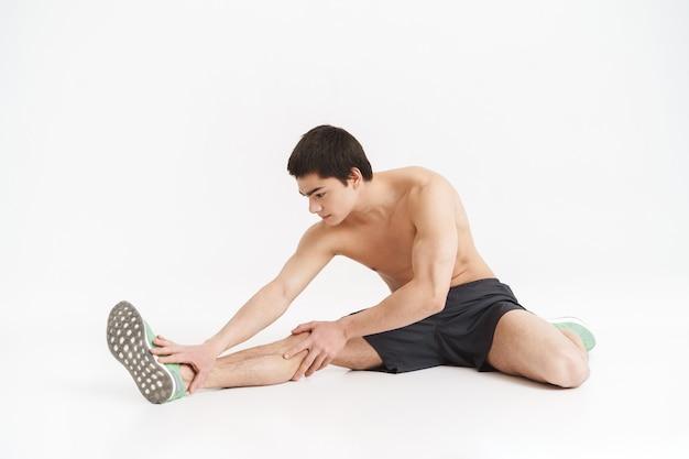 Ritratto integrale di un giovane sportivo in forma sana che si riscalda prima di fare jogging su bianco