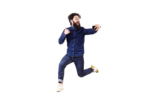 Ritratto integrale di un uomo barbuto gioioso hipster, saltando e prendendo selfie, isolato