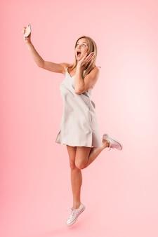Ritratto integrale di gioiosa giovane donna che sorride alla macchina fotografica mentre prende selfie ritratto su smartphone isolato su parete rosa