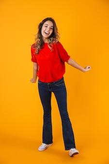 Ritratto a figura intera di una giovane donna allegra e allegra adorabile in piedi isolata sul muro giallo, in posa