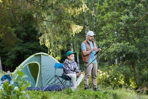 Ritratto integrale di amorevole padre e figlio che pescano in riva al lago insieme durante il viaggio in campeggio in natura, copia spazio