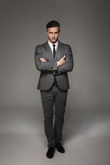 Ritratto integrale dell'uomo maschile che indossa tailleur in posa con sguardo serio mantenendo le braccia conserte, isolato sopra il muro grigio