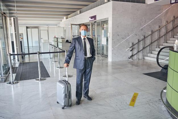 Ritratto a figura intera di maschio maturo in abito elegante e maschera in piedi in corridoio con valigia