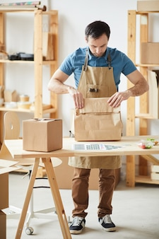 Ritratto integrale dell'uomo maturo che indossa gli ordini di imballaggio del grembiule mentre fa una pausa la tavola di legno, lavoratore di servizio di consegna del cibo