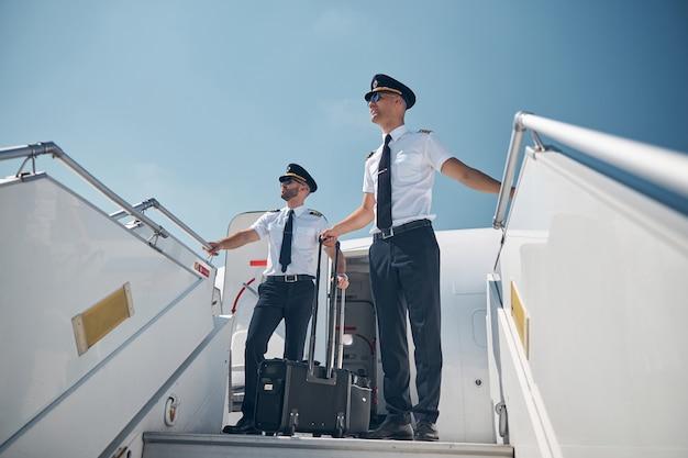 Ritratto a figura intera di colleghi uomini in uniforme in piedi sulla rampa mobile all'aperto