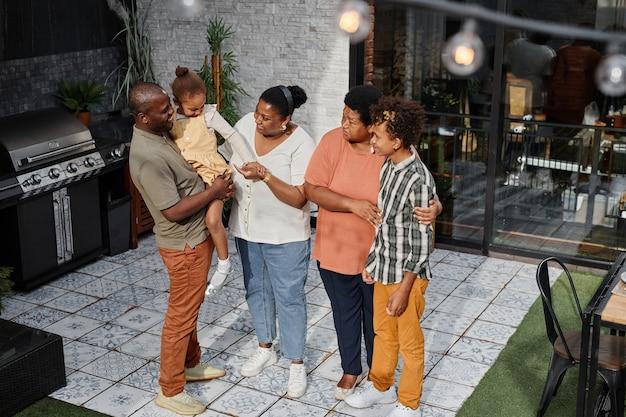 Ritratto a figura intera di una moderna famiglia afroamericana che chiacchiera in terrazza durante una festa barbecue all'aperto