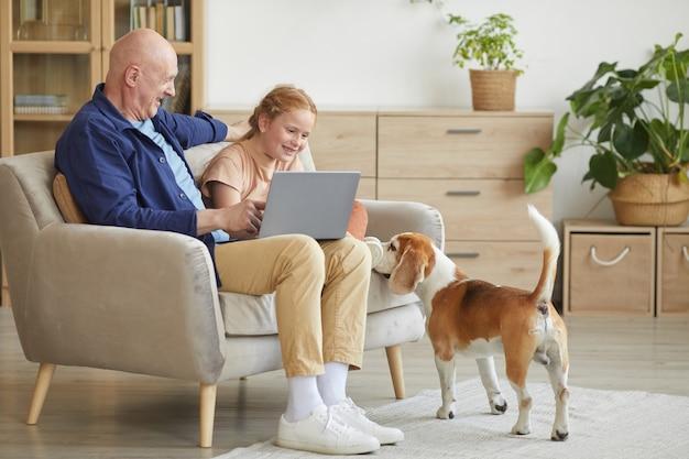 Ritratto integrale dell'uomo anziano moderno che gode del tempo a casa con la ragazza dai capelli rossi cura e il cane da compagnia