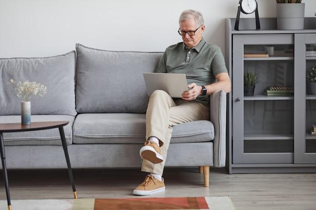 Ritratto a figura intera di un uomo anziano moderno che utilizza il computer portatile a casa mentre è seduto sul divano in interni minimi, copia spazio