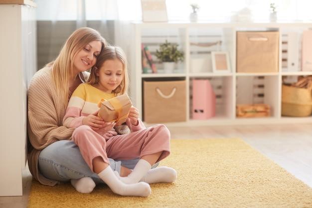 Ritratto integrale della madre e della figlia che tengono presente mentre sedendosi sul pavimento nell'interno accogliente della stanza dei bambini, lo spazio della copia