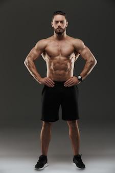 Ritratto integrale di una posa muscolare motivata dell'uomo