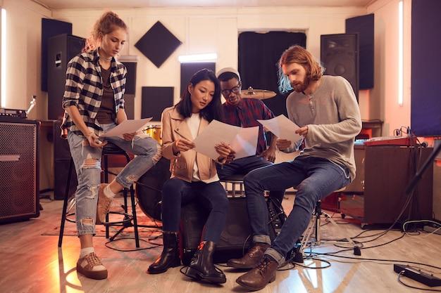 Ritratto a figura intera di una band multietnica che scrive musica insieme, tutti in possesso di fogli di testo