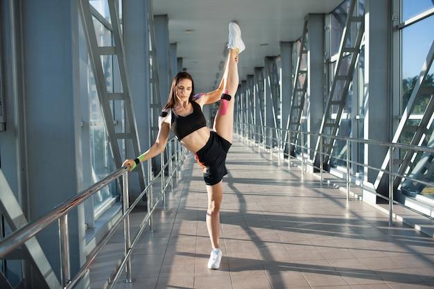 Ritratto integrale della donna castana muscolare che pratica spaccatura. giovane atleta femminile flessibile in posa con la gamba in alto, tenendo il corrimano all'interno, nastro kinesiologico colorato sul corpo, interni futuristici.