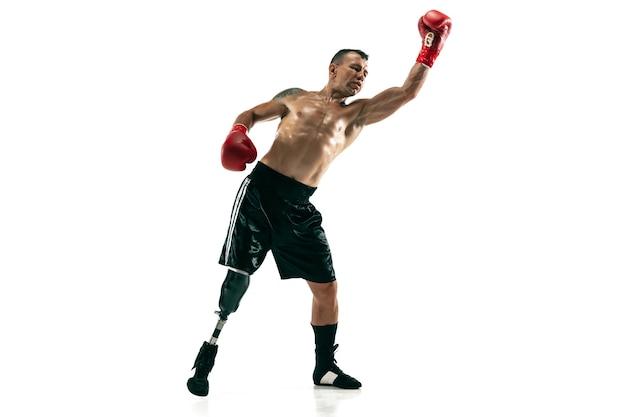 Ritratto integrale dello sportivo muscolare con la gamba protesica, spazio della copia. pugile maschio in guanti rossi. colpo isolato sul muro bianco.