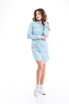Ritratto integrale di bella giovane donna pensierosa con capelli ricci in camicia lunga dei jeans e scarpe da tennis bianche che stanno sopra la parete bianca