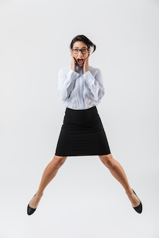 Ritratto integrale di una bella donna d'affari che salta isolato sopra il muro bianco, celebrando il successo
