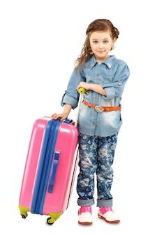 Ritratto integrale di una bambina graziosa con la grande valigia rosa su ruote isolate su bianco
