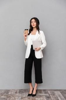 Ritratto integrale di una bella giovane donna vestita in giacca e pantaloni in piedi su sfondo grigio, bere caffè, portare tablet