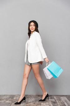 Ritratto integrale di una bella giovane donna vestita in minigonna e giacca su sfondo grigio, portando borse della spesa, camminando