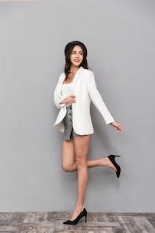 Ritratto integrale di una bella giovane donna vestita in minigonna e giacca che cammina su sfondo grigio, guardando lontano