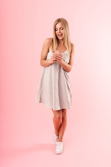 Ritratto a figura intera di una bella giovane donna che indossa un vestito sorridente mentre tiene in mano uno smartphone isolato su un muro rosa