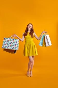 Il ritratto a figura intera di una donna modello dai capelli rossi porta molti pacchi godendosi lo shopping di vendita all'estero, indossando un abito giallo alla moda e scarpe col tacco alto isolate su sfondo giallo, posando alla telecamera, sorridente
