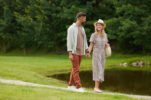 Ritratto integrale della coppia adulta romantica che si tiene per mano mentre si cammina in riva al lago in uno scenario di campagna rustica