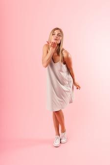 Ritratto a figura intera di una giovane donna seducente che indossa un vestito che flirta e che soffia aria bacio alla telecamera isolata sul muro rosa in studio