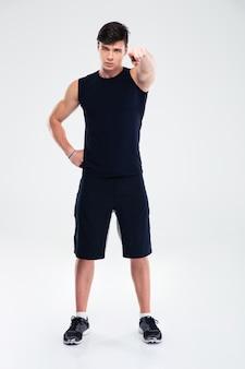 Ritratto integrale di un uomo serio di forma fisica che indica dito alla macchina fotografica isolata