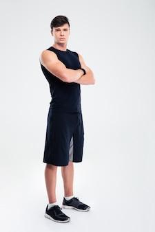Ritratto a figura intera di un uomo serio di fitness in piedi con le braccia conserte isolate