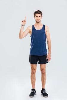 Ritratto a figura intera di un uomo sportivo serio che si presenta su qualcosa su sfondo grigio
